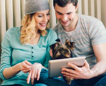 Couple looking holding puppy looking at a tablet